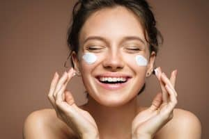 happy woman applying face cream