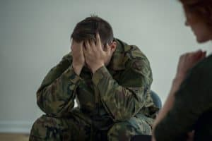 distressed soldier putting his hands over his face talking to therapist