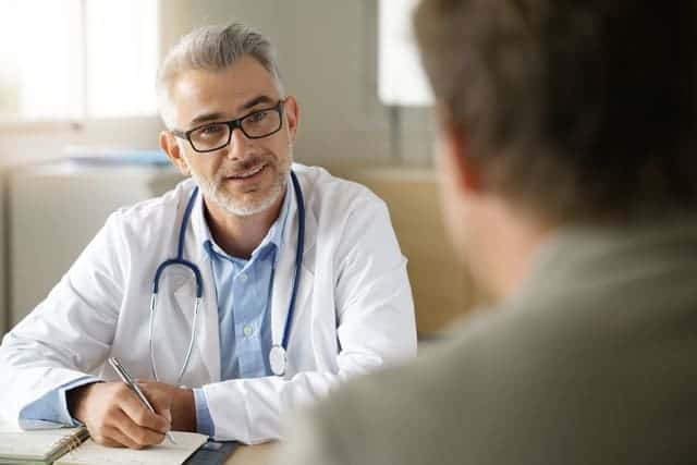handsome doctor wearing glasses speaking with patient