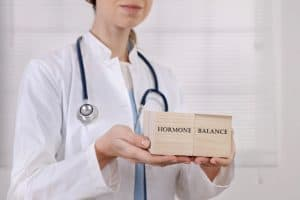 doctor holding blocks that say hormone balance