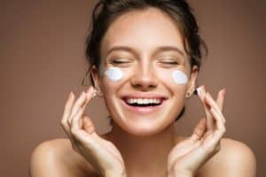 happy woman putting on face cream