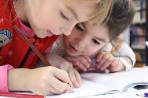 two young girls focusing on writing something down