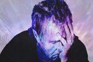 color edited purple picture of man holding head in pain