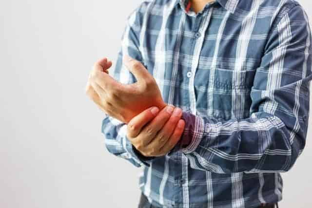 man clutching his painful wrist