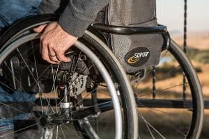 man sitting in wheel chair with one hand on the wheel