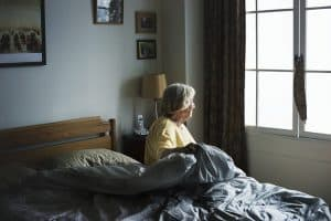 old woman sitting in bed looking out the window