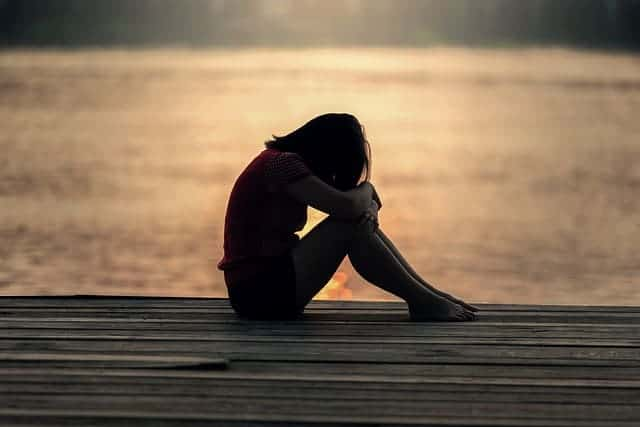 sad teen girl sitting on a dock by a lake
