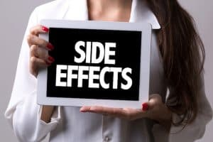"Woman holding a ""SIDE EFFECTS"" sign"