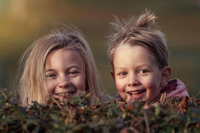 Two Smiling Kids Looking over from Behind Some Bushes