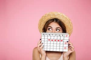 woman holding up a menstrual calendar