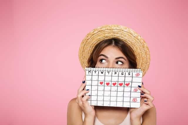 woman holding up a menstrual calendar