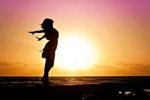 woman exalting happily during sunset at the beach