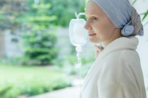woman with cancer wearing a head covering standing by the window