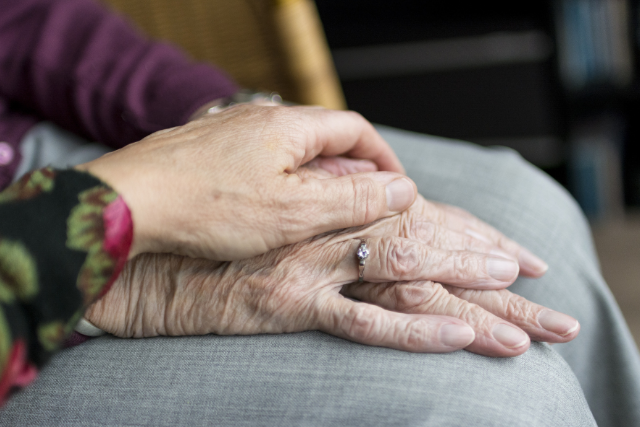 elderly woman laying her hand on top of another's