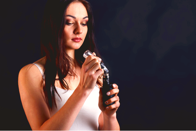 Woman refilling an e-cigarette with vape oil