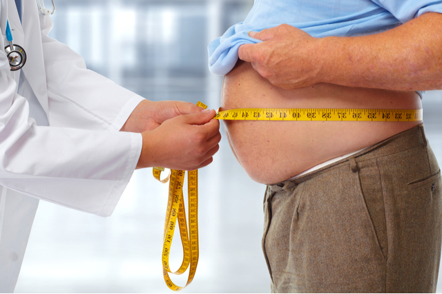 Man lifts his shirt as doctor measures his waist circumference w/ a tape measure