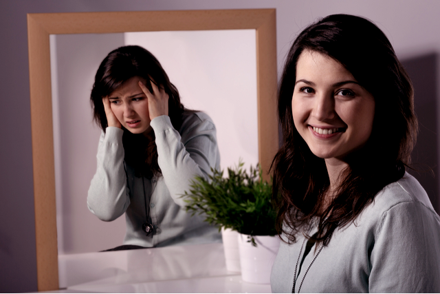 Picture shows a bipolar woman smiling, while her reflection in a mirror beside her shows her clutching her head in distress.