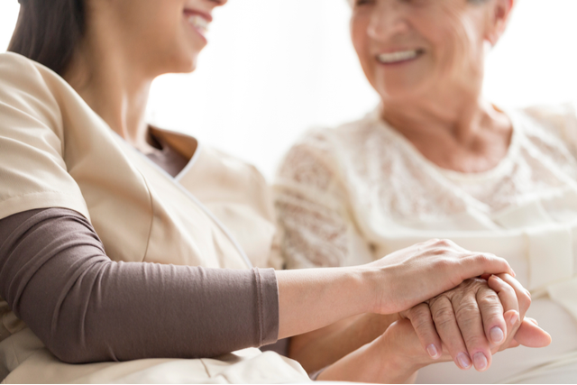 Woman reassuring an elderly by holding their hand