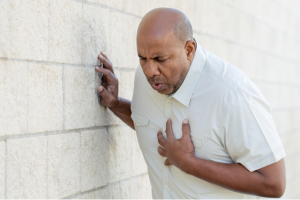 A man leaning against a brick wall is clutching his chest in discomfort