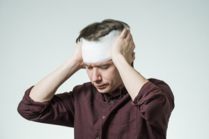 Man firmly pressing on both sides of his bandage-wrapped head