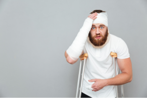Man in crutches with bandages on his right arm & around his head, looking surprised with his hand over his forehead.